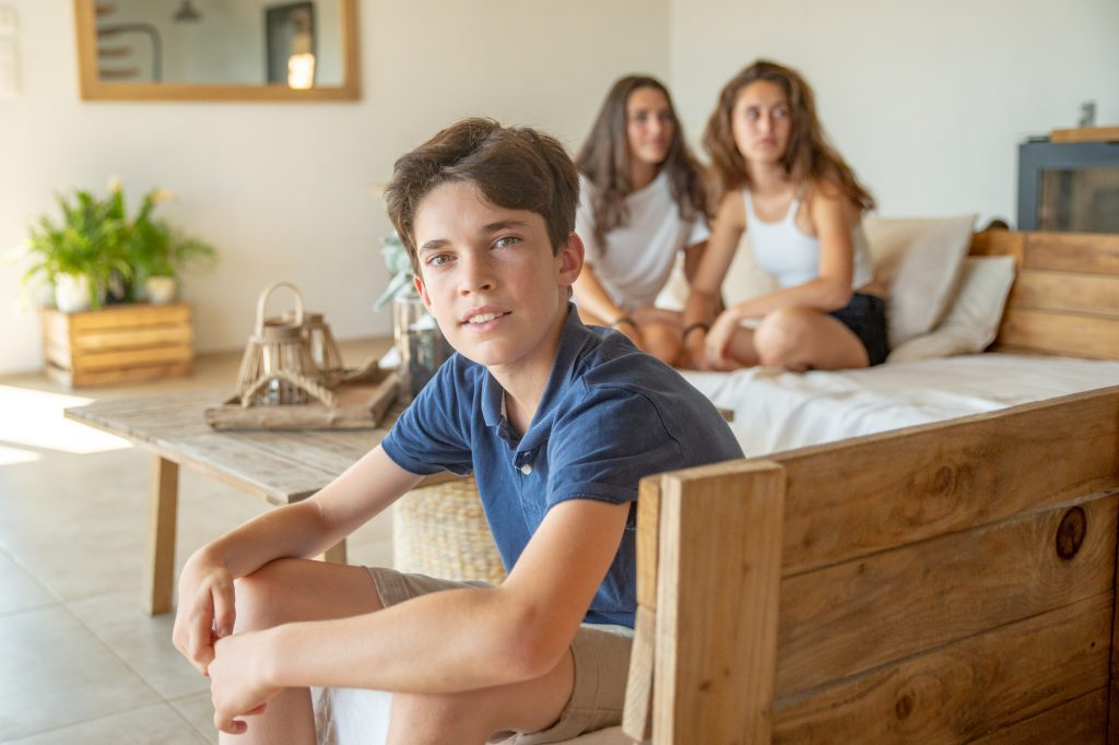 Portrait d'un frère et ses 2 soeurs en arrière plan, à leur domicile. Photo Studio Polidori