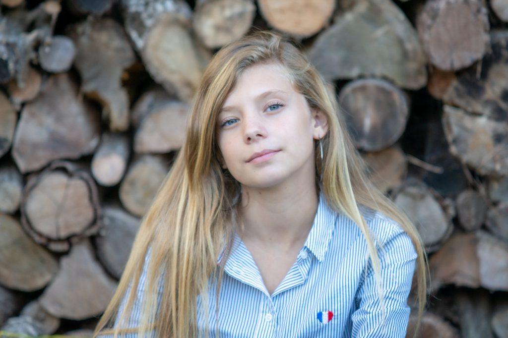 Une jeune fille pose devant des bûches, photo à domicile. Photo Studio Polidori