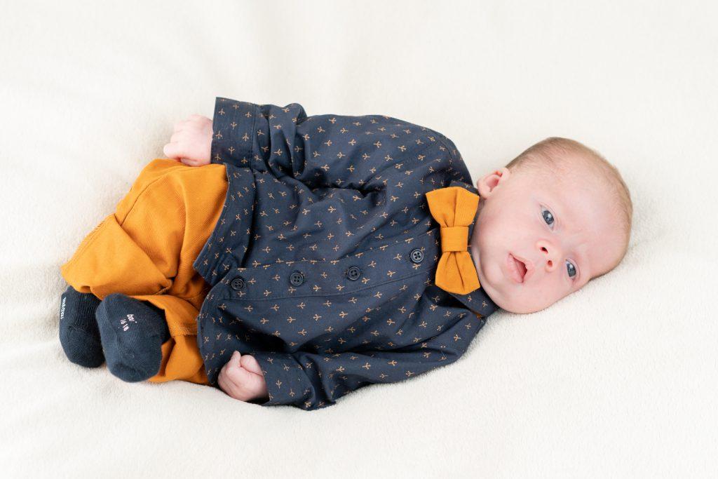Bébé avec noeud papillon, allongé, yeux grands ouverts. Photo Studio Polidori