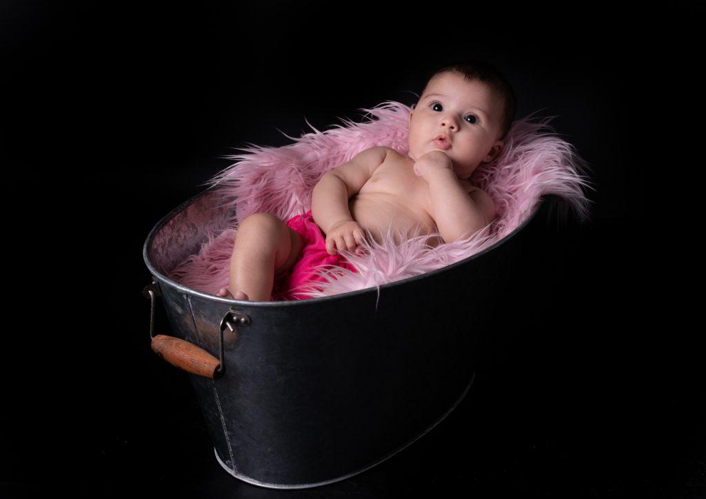 Le bébé nous regarde, allongé paisiblement dans une bassine en zinc et fourrure rose. Photo Studio Polidori