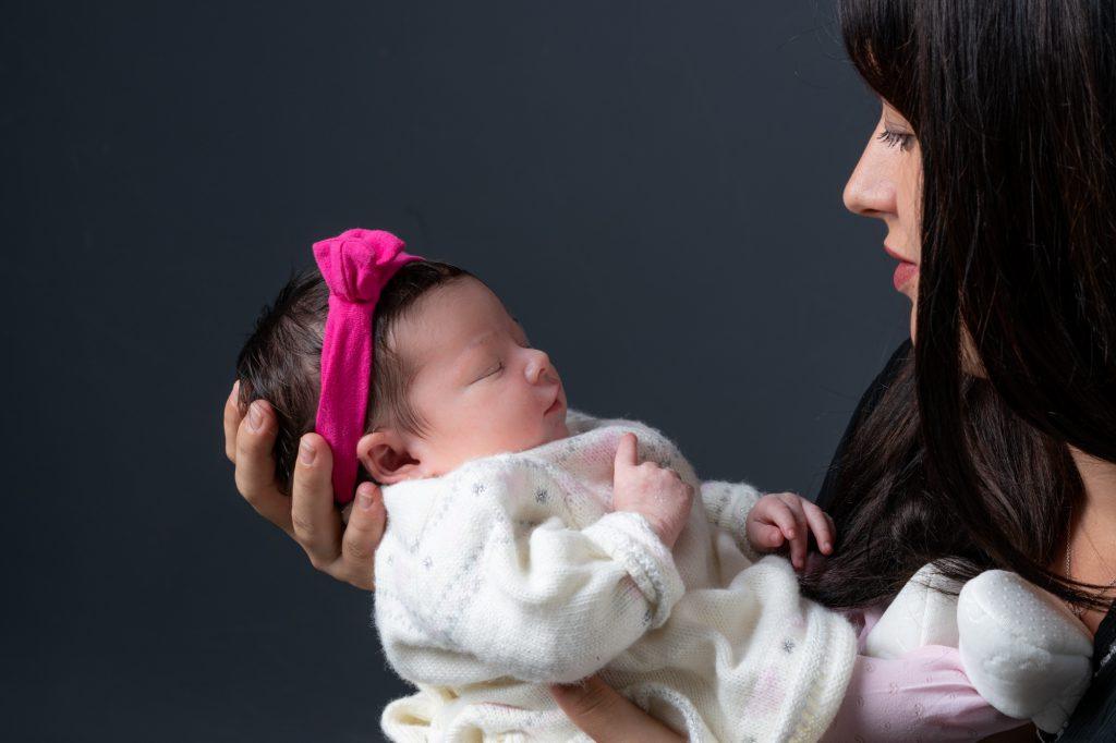 Maman regardardant son bébé endormi dans ses bras. Au studio, fond noir. Photo Studio Polidori