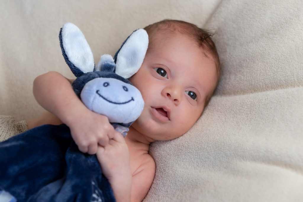 Bébé grands yeux ouverts, tenant femement son doudou. Photo Studio Polidori