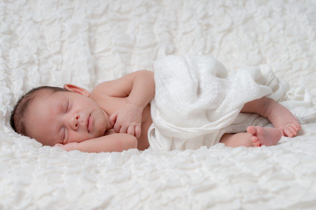 Bébé dormant sur le côté, tête posée sur son épaule. Photo Studio Polidori