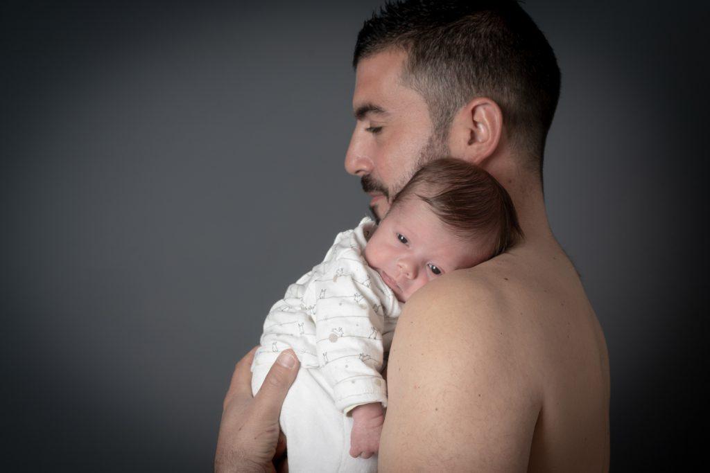 Bébé yeux grands ouverts, calé sur l'épaule de son papa. Photo Studio Polidori