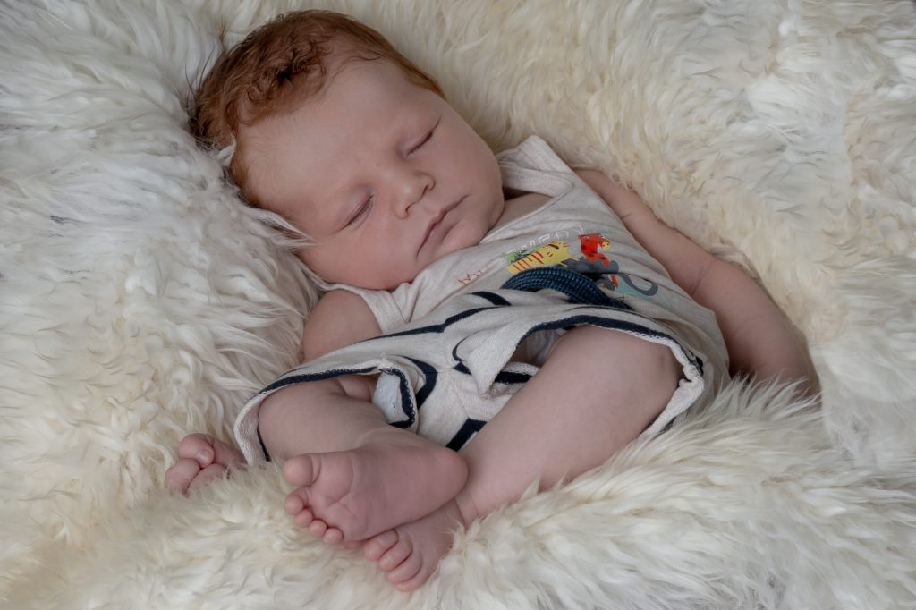 Bébé rouquin endormi dans peau de mouton. Phto Studio Polidori
