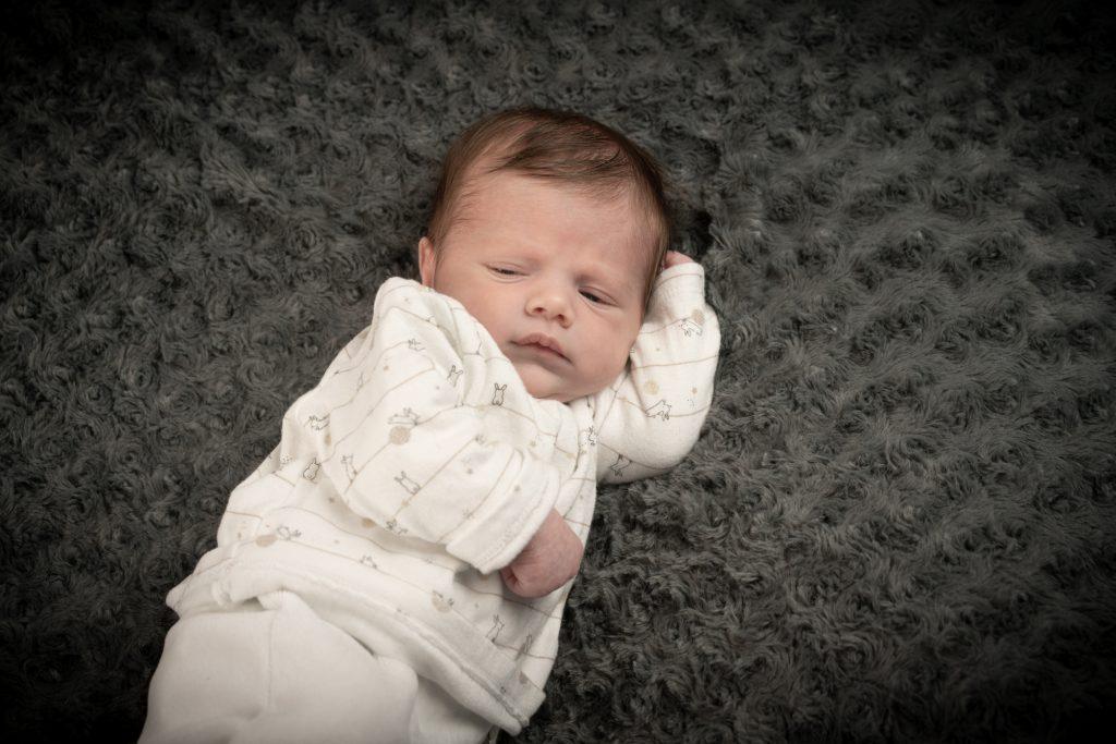Bébé se posant, la tête appuyée au creux de son coude. Photo Studio Polidori