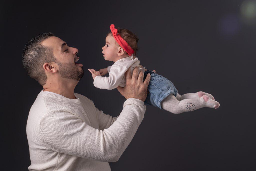 Papa fait voler bébé dans ses bras, Regard entre les 2. Photo Studio Polidori