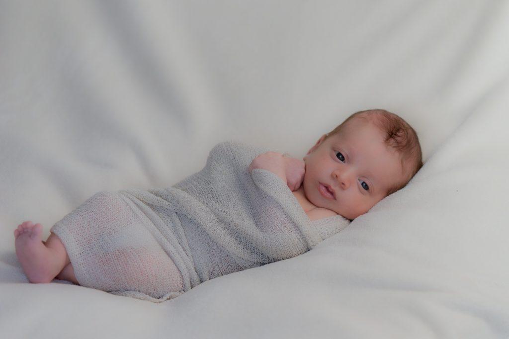 Bébé bien enroulé dans son wrap, yeux grand ouvert