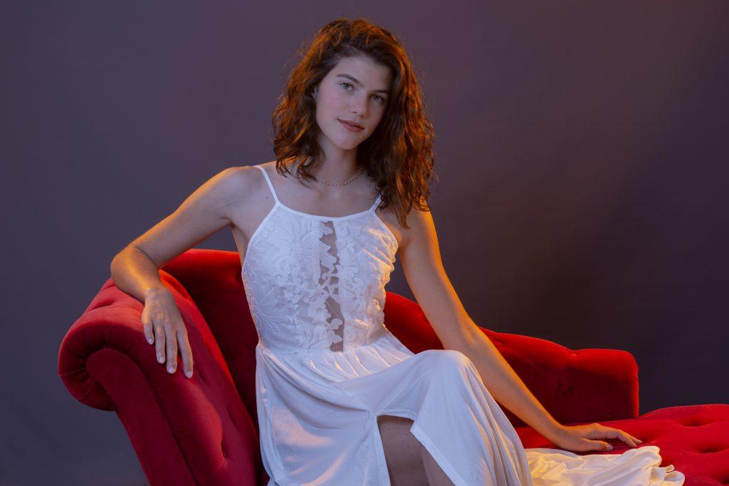 Une jeune femme , avec robe blanche, assise sur méridienne rouge. Photo Studio Polidori