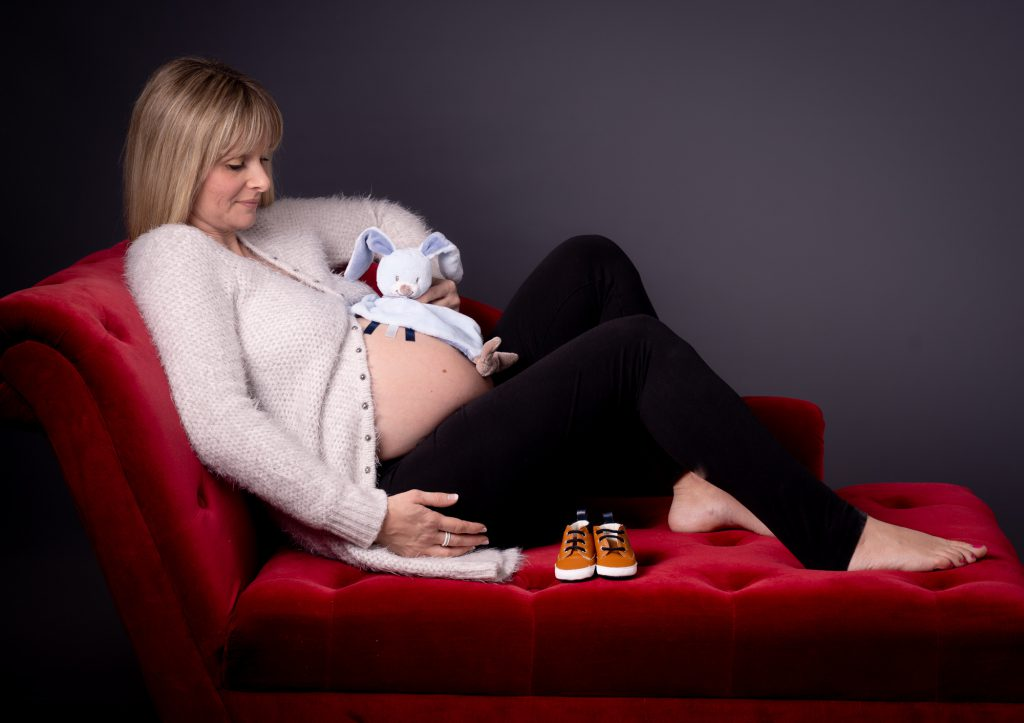Allongée sur méridienne, femme enceinte avec les chaussures et doudou du bébé tant attendu. Photo Studio Polidori