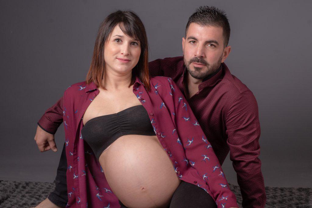 Femme enceinte et futur papa assis au sol. Photo Studio Polidori