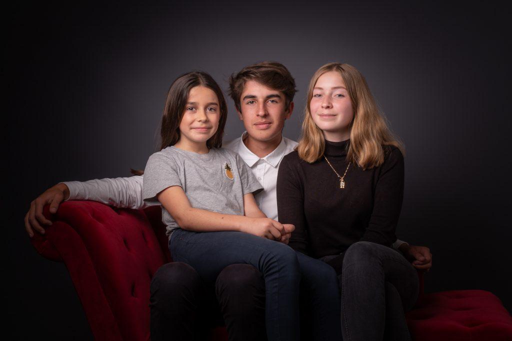 Le grand frère est entouré de ses 2 soeurs. Photo Studio Polidori