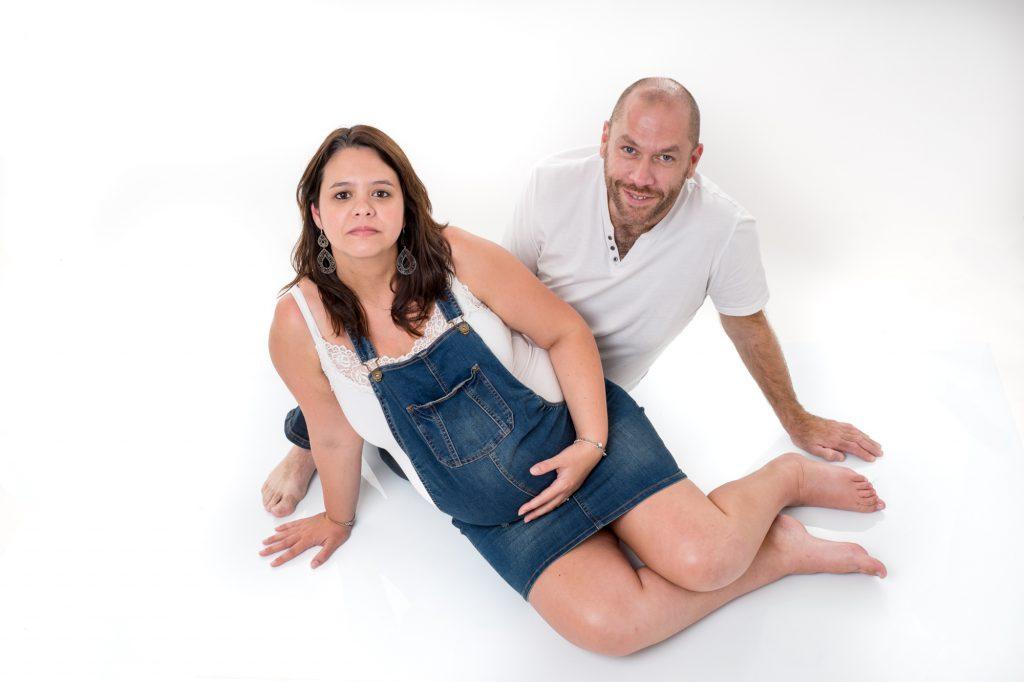 Photo au studio sur fond blanc, couple au sol regardant en l'air. Grossesse maman avec papa. Photo Studio Polidori