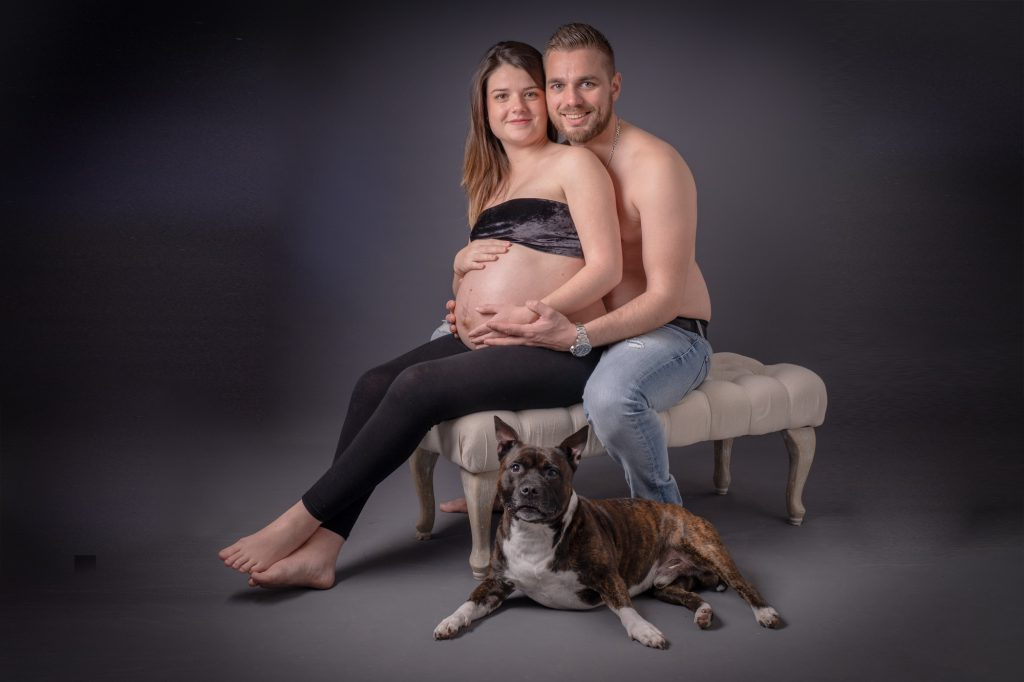 Un jeune couple avec madame enceinte assis, leur chien à leurs pieds. Photo Studio Polidori