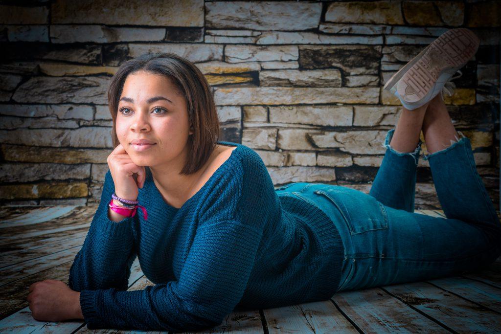 Une jeune femme pose décontractée allongée, devant mur de briques. Photo Studio Polidori
