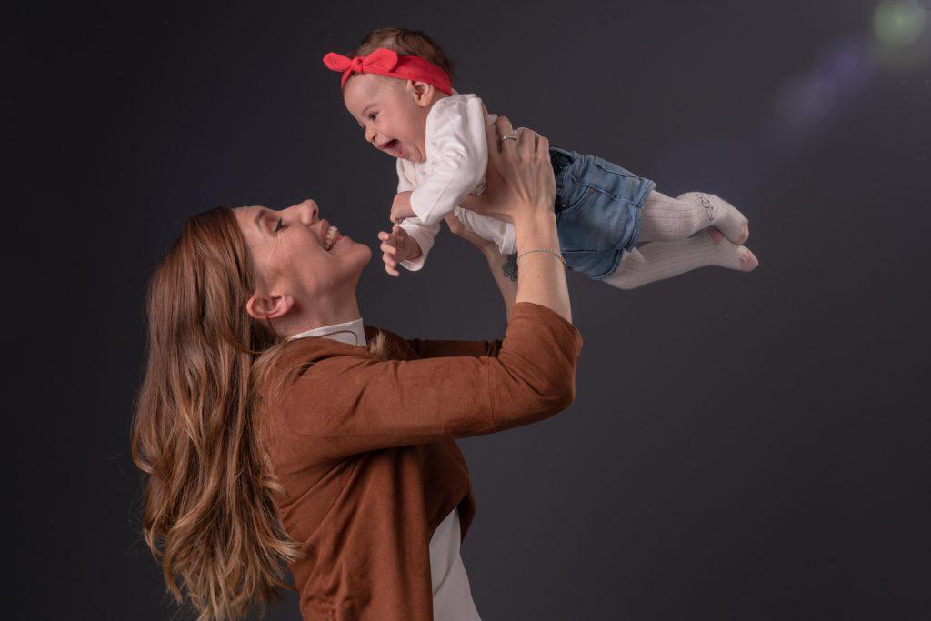 Maman s'éclate avec sa petite fille en la faisant voler. Enorme sourire et rire des 2. Photo Studio Polidori
