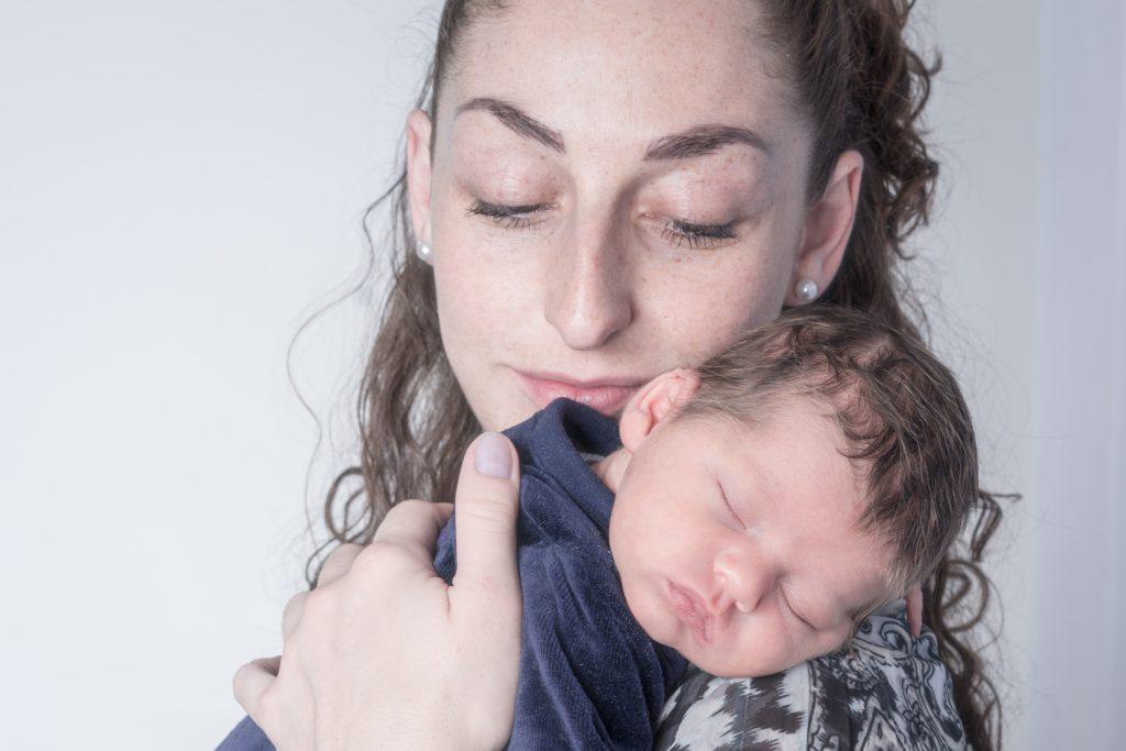 Regard tendre d'une maman sur son bébé, endormi sur son épaule. Photo Studio Polidori
