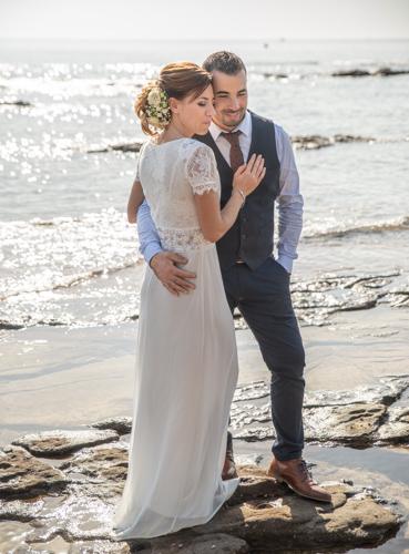 Couple de mariés posant sur les rochers au bord de l'eau, plage de Boulouris. Photo Studio Polidori