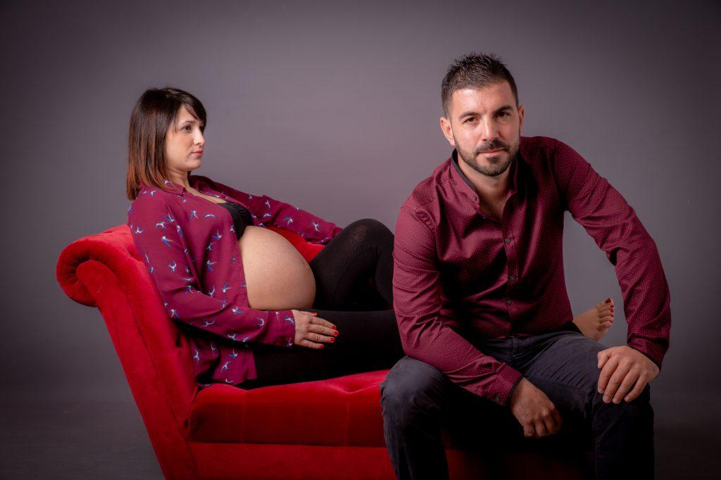 Futur papa assis avec madame enceinte (ventre rond) en arrière plan). Photo Studio Polidori