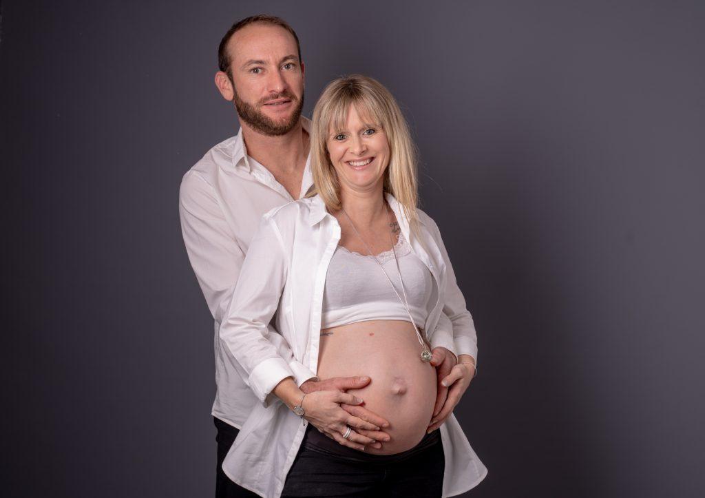 Papa et future maman se tenant les mains sur le ventre rond. Photo Studio Polidori