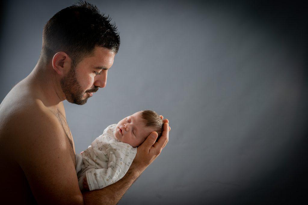 Regard tendre d'un papa envers son bébé, qui s'est endormi sur ses avant-bras. Photo Studio Polidori