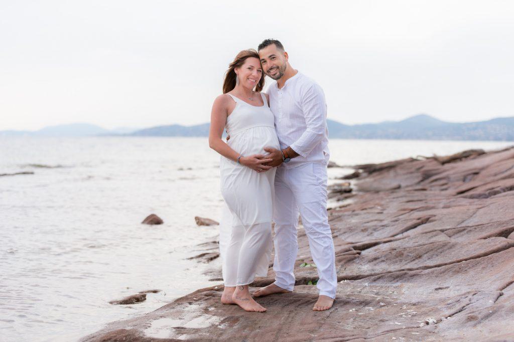 Sur les rochers de Boulouris, au bord de mer, papa et future maman enlacés unissant leurs mains sur ventre rond