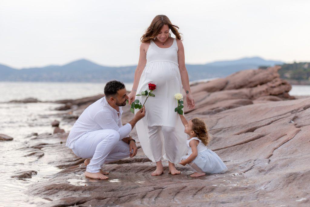 Sur les rochers au bord de mer, à Boulouris. Petit fille et papa offrent des fleurs au ventre rond de maman enceinte. Photo Studio Polidori