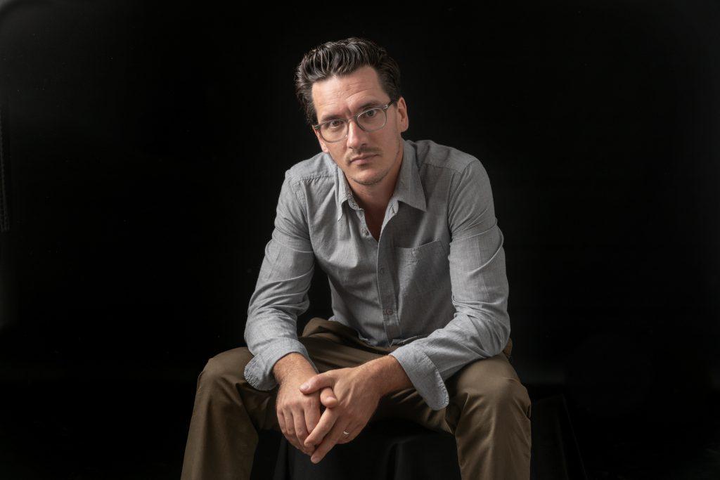 Un homme avec des lunettes est assis au studio sur fond noir