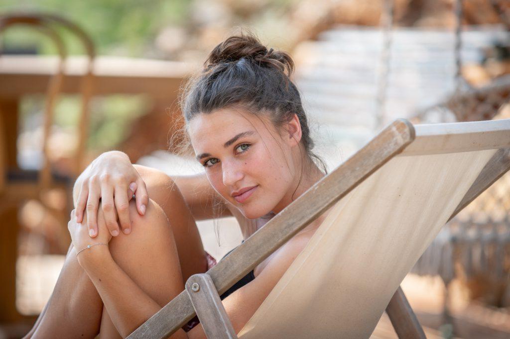 Jeune femme assise dans chilienne, se retournant. Photo Studio Polidori