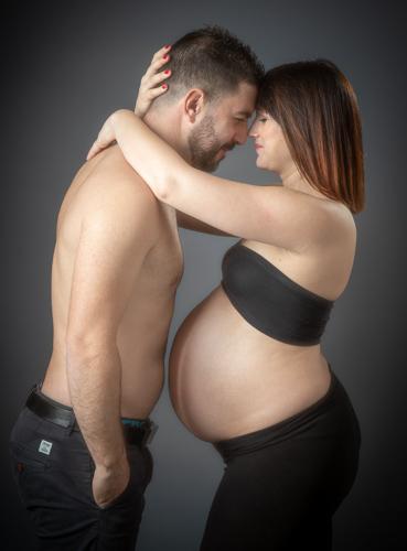 Future maman tendrement front contre front avec le futur papa. Ventre rond contre ventre ventre plat. Photo Studio Polidori