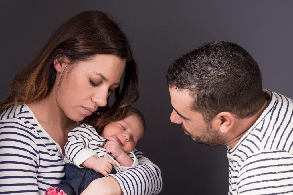 Papa et maman regarde bébé souriant. Toute la famille porte un pull marin. Photo Studio Polidori