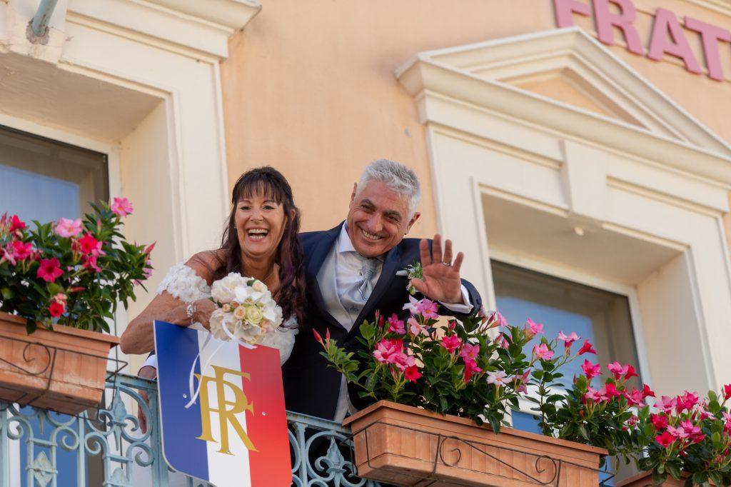 Les mariés au balcon de la mairie du Muy (rire et signe de main). Photo Studio Polidori
