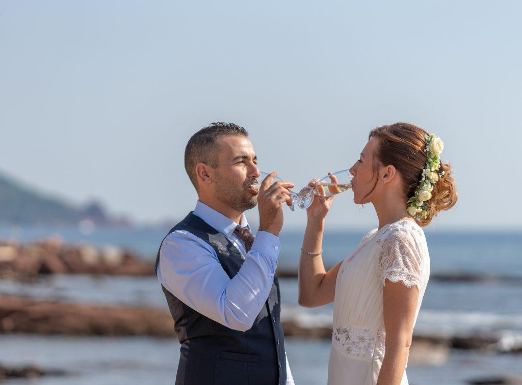 A la plage de Boulouris, les mariés partagent une coupe de champagen avec la mer en toile de fond. Photo Studio Polidori
