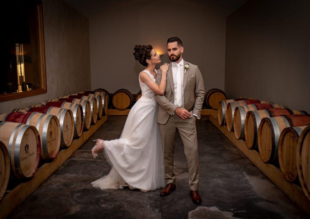 Les mariés sont devant les fûts de chêne au Château Vaudois à Roquebrune sur Argens. La mariée s'appuie tendrement sur le marié, qui reste impassible. Photo Studio Polidori