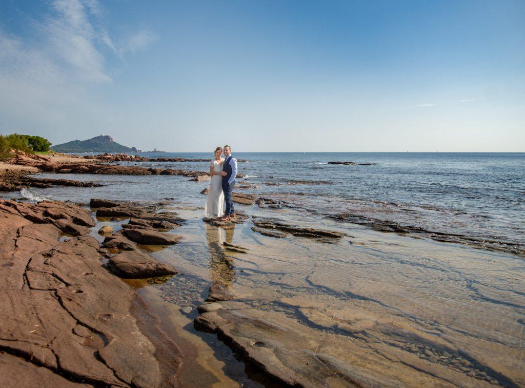 Les mariés sont dans les rochers devant la mer à Boulouris, avec l'île d'Or au fond. Photo Studio Polidori