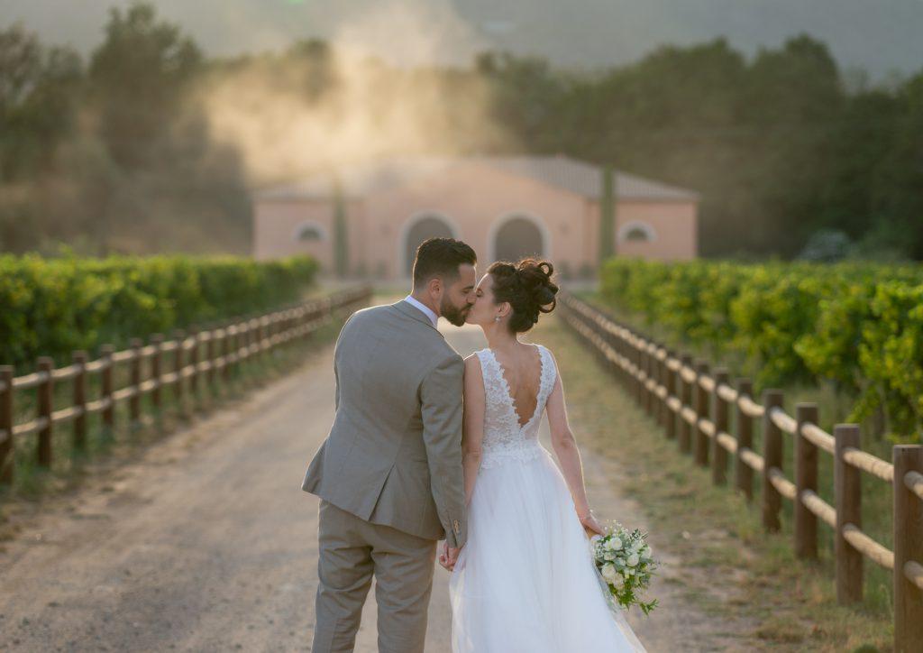 Les mariés , de dos, s'embrassent dans les vignes, avec tourbillon de sable. Au Château Vaudois à Roquebrune sur Argens. Photo Studio Polidori