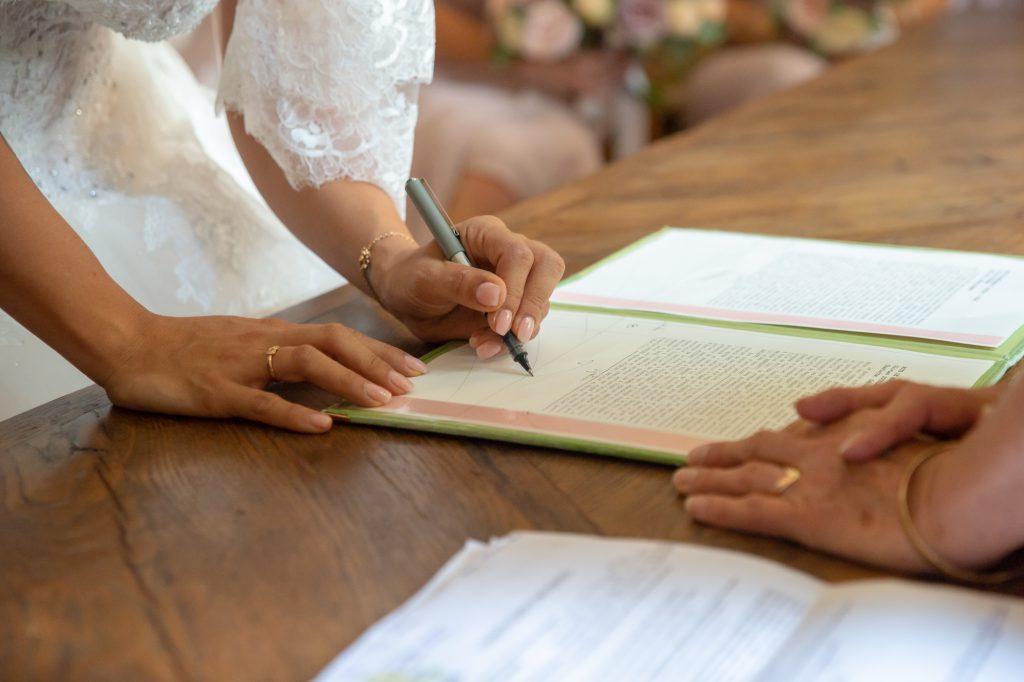 Main de la mariée signant l'acte de mariage. Photo Studio Polidori